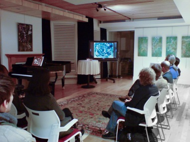 Music lovers watch a film of Christina's paintings inspired by Constantine's music, at the Canadian Music Centre.